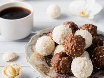 Caramelle della noce di cocco e del cioccolato in una ciotola su un'orchidea di legno della tazza di caffè del vassoio Fotografie Stock Libere da Diritti