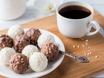 Caramelle della noce di cocco e del cioccolato in una ciotola su un'orchidea di legno della tazza di caffè del vassoio Immagini Stock