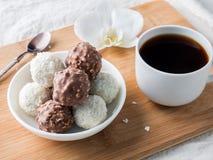 Caramelle della noce di cocco e del cioccolato in una ciotola su un'orchidea di legno della tazza di caffè del vassoio Fotografia Stock Libera da Diritti