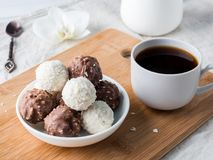 Caramelle della noce di cocco e del cioccolato in una ciotola su un'orchidea di legno della tazza di caffè del vassoio Immagini Stock Libere da Diritti