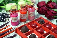 Caramelle di cioccolato del cuore, candele rosse, bottiglie sveglie con felicità, pozione di amore ed elisir magico immagine stock libera da diritti