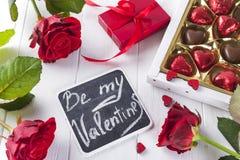 Caramelle di cioccolato deliziose in contenitore di regalo su fondo di legno bianco Fotografie Stock
