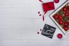 Caramelle di cioccolato deliziose in contenitore di regalo su fondo di legno bianco Immagine Stock