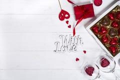 Caramelle di cioccolato deliziose in contenitore di regalo su fondo di legno bianco Immagini Stock