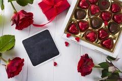 Caramelle di cioccolato deliziose in contenitore di regalo su fondo di legno bianco Immagini Stock Libere da Diritti