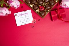 Caramelle di cioccolato deliziose in contenitore di regalo su fondo rosso Fotografie Stock Libere da Diritti