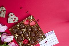Caramelle di cioccolato deliziose in contenitore di regalo su fondo rosso Immagini Stock