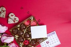 Caramelle di cioccolato deliziose in contenitore di regalo su fondo rosso Fotografia Stock
