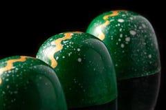 Caramelle di cioccolato fatte a mano di lusso su fondo nero Caramelle verdi con le gocce multicolori Concetto di prodotto per Fotografie Stock