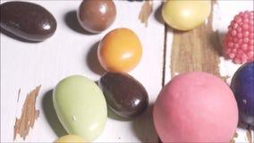 Caramelle dolci variopinte sulla superficie bianca di legno del granaio, filtrante stock footage