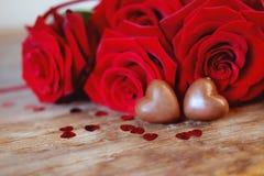 Caramelle e rose rosse del cuore del cioccolato del presente di giorno del ` s del biglietto di S. Valentino Immagini Stock