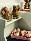 Caramelle e supporto della tenuta di Gingermen di Natale sopra i bigné Immagine Stock Libera da Diritti