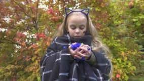 Caramelle estatiche e dancing della tenuta della ragazza all'aperto, godendo della festa di Halloween archivi video