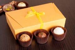 Caramelle fatte a mano del cioccolato su una tavola nera Contenitore di cioccolato fotografie stock