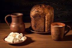 Caramelle gommosa e molle bianche, pane casalingo, una brocca dell'argilla, una teiera e un g Fotografia Stock Libera da Diritti