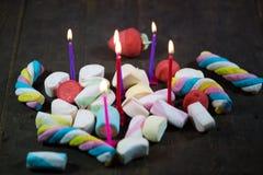 Caramelle gommosa e molle con le candele, fondo di legno Fotografia Stock