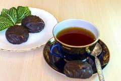 Caramelle gommosa e molle del cioccolato e una tazza di t? nero fotografie stock