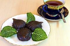 Caramelle gommosa e molle del cioccolato e una tazza di t? nero immagini stock