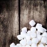 Caramelle gommosa e molle rotonde lanuginose bianche su fondo d'annata di legno w Immagine Stock