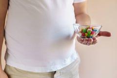 Caramelle mangiarici di uomini di peso eccessivo alimento di ingrassamento fotografie stock libere da diritti