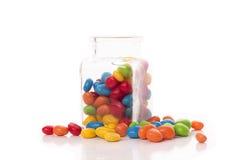 Caramelle multicolori su un fondo bianco che cade da un vetro Immagini Stock