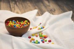 Caramelle multicolori un vaso di legno Immagini Stock