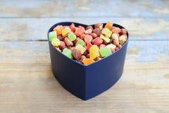 Caramelle in una scatola a forma di del cuore Fotografie Stock