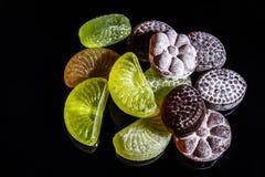 Caramelle variopinte con tagliente di frutta deliziosa fotografie stock libere da diritti