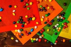 Caramelle variopinte su una tavola di legno con i tovaglioli colorati Immagine Stock Libera da Diritti