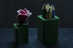 caramelo color de rosa grande en un fondo oscuro con los lápices coloridos en cajas verdes Fotos de archivo libres de regalías