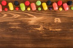 Caramelo coloreado en fondo de madera oscuro con el copespace Imagen de archivo