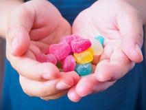 Caramelo colorido de los corazones en las manos para el fondo de las tarjetas del día de San Valentín Imágenes de archivo libres de regalías