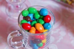 Caramelo colorido Dulces coloreados multi Caramelo coloreado en un vidrio El chocolate redondo es muy colorido Imagenes de archivo