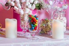 Caramelo colorido Dulces coloreados multi Caramelo coloreado en un vidrio El chocolate redondo es muy colorido Vela Foto de archivo libre de regalías