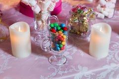Caramelo colorido Dulces coloreados multi Caramelo coloreado en un vidrio El chocolate redondo es muy colorido Vela Foto de archivo