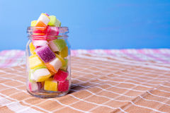 Caramelo colorido en tarro en la tabla con el fondo azul Foto de archivo libre de regalías