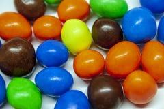 Caramelo de chocolate colorido en un fondo blanco imagen de archivo