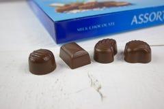 Caramelo de chocolate con la caja azul del chocolate en la madera blanca Fotos de archivo libres de regalías