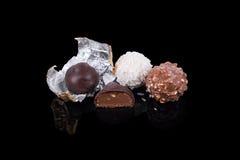 Caramelo de chocolate en diversos colores y formas superficiales negros reflexivos Chocolates hechos a mano Fotos de archivo