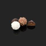 Caramelo de chocolate en diversos colores y formas superficiales negros reflexivos Chocolates hechos a mano Imagen de archivo libre de regalías