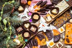 Caramelo de chocolate, fruta cítrica escarchada, naranjas con símbolos de la Navidad Fotografía de archivo libre de regalías