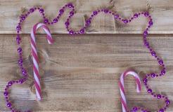 Caramelo de la Navidad y guirnalda rosada en un fondo de madera Imagen de archivo