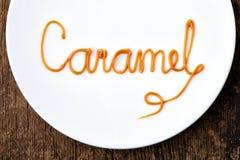 Caramelo de la palabra en la placa blanca imagenes de archivo