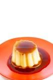 Caramelo de nata en la placa roja Fotografía de archivo