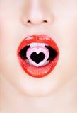 Caramelo del corazón en labios rojos. Caramelo del corazón en labios rojos. Imágenes de archivo libres de regalías