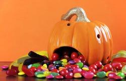 Caramelo del truco o de la invitación que se derrama fuera de la calabaza de Halloween Imagen de archivo libre de regalías