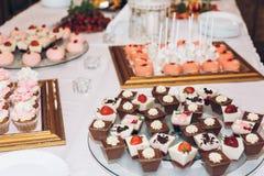 Caramelo delicioso, dulces, magdalenas, estallidos adornadas con las flores en t Imagenes de archivo