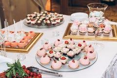 Caramelo delicioso, dulces, magdalenas, estallidos adornadas con las flores en t Foto de archivo
