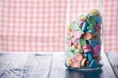 Caramelo dulce colorido en garrafa del vino en la tabla de madera Fotografía de archivo libre de regalías