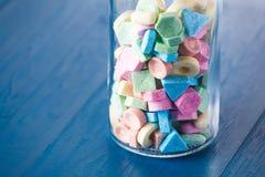 Caramelo dulce colorido en una garrafa del vino Foto de archivo